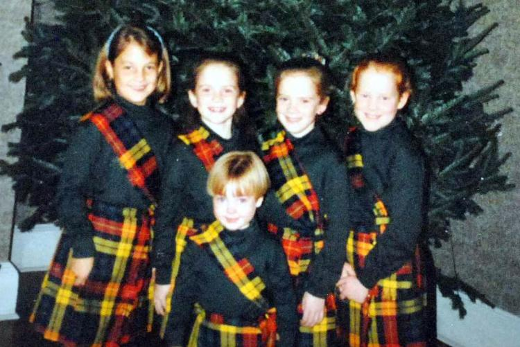 Five grandchildren pose in front of the Christmas evergreen at Government House