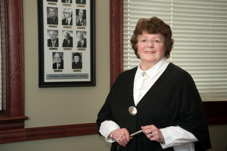 Nancy Guptill as chair of the Worker's Compensation Board stands in front of a composite of former chairpersons
