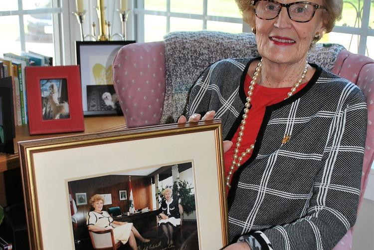 Catherine Callbeck holding image of herself and Kim Campbell as Canada's only female prime minister