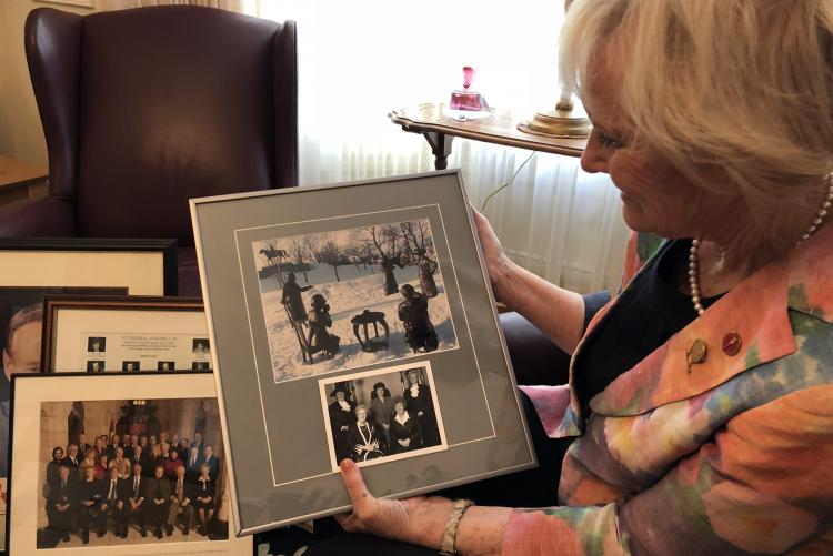Libbe Hubley holds a frame image in her living room
